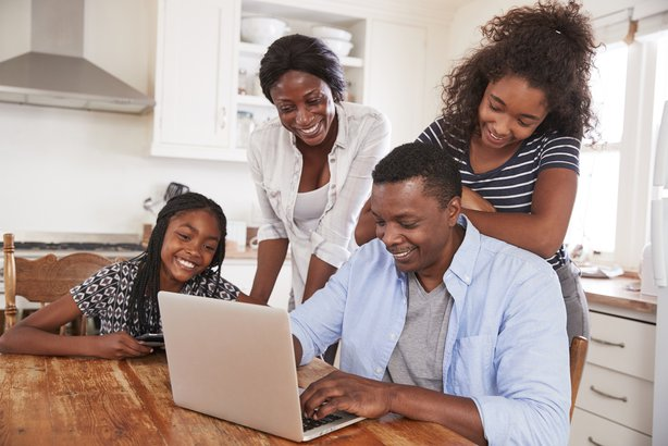family around kitchen table on laptop together