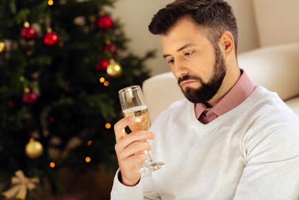man looking uneasily at glass of champagne with christmas tree in background