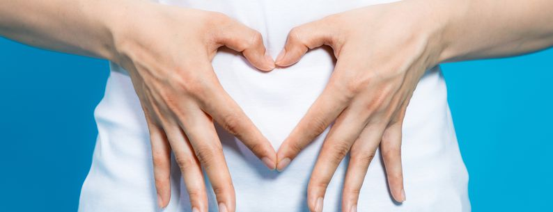 woman who makes a heart shape by hands on her stomach