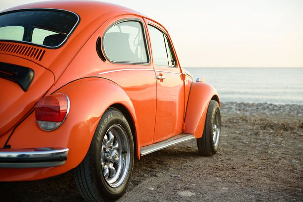 classic orange Volkswagen beetle on sea coast