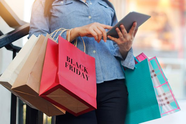 woman with tablet and black friday shopping bags