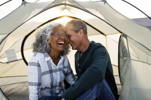 senior couple whispering to each other and smiling in camping tent