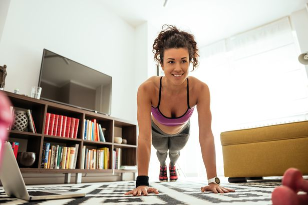 healthy mixed-race woman doing push-ups at home