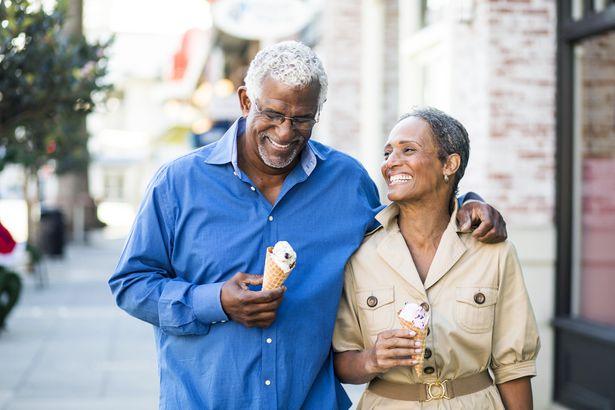 senior couple eating ice cream walking down the street, neither wearing wedding rings