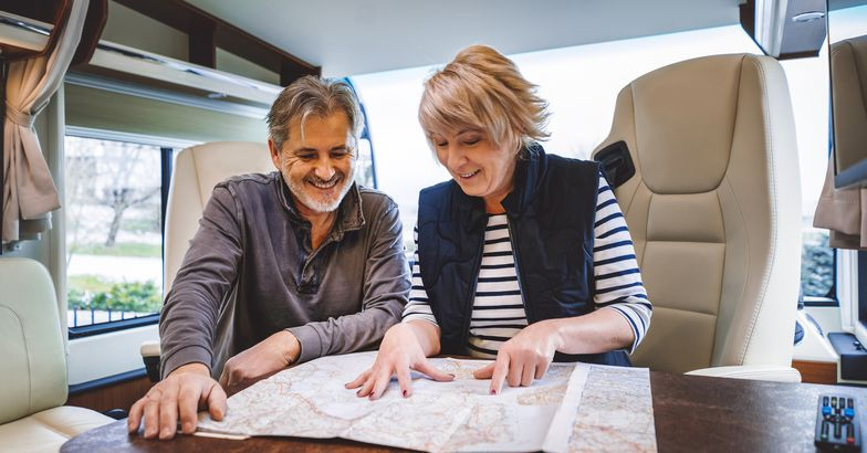 smiling couple looking at map on table in rv