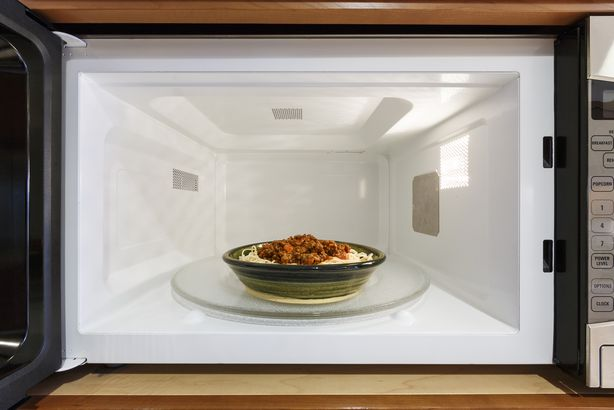 spaghetti in bowl in opened microwave