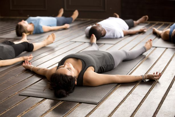 group of people doing corpse pose in yoga studio