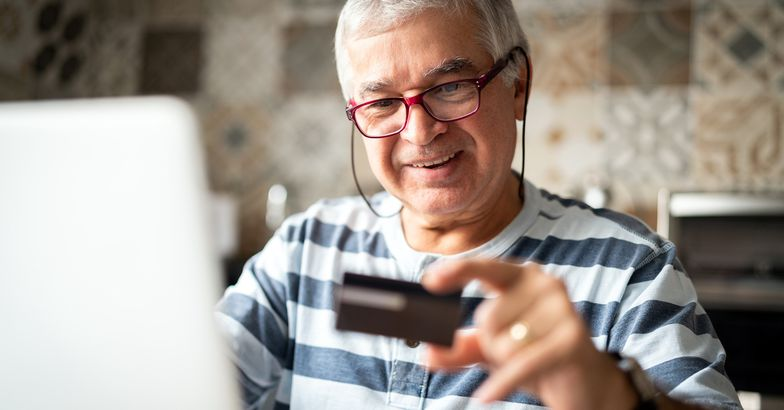 senior man holding credit card smiling with laptop open