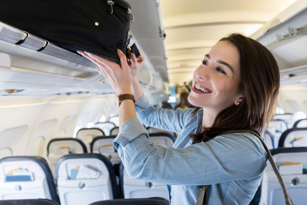 woman places luggage in airplane's overhead compartment