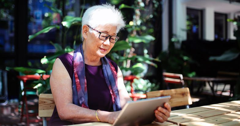 senior woman using tablet, seated at outdoor table