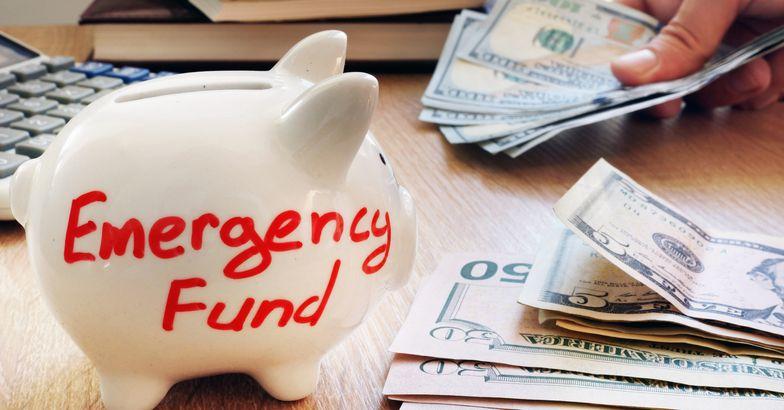 emergency fund piggy bank, cash beside it