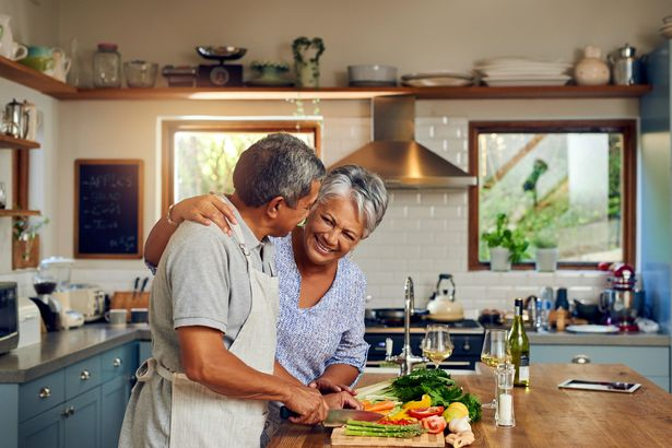 middle-aged couple making healthy dinner in kitchen smiling