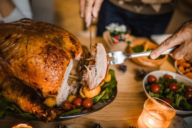 man carving roasted Thanksgiving turkey