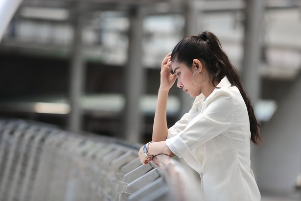 woman leaning over railing with worried expression
