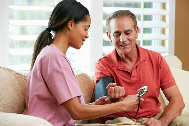 nurse checking blood pressure of an elderly man
