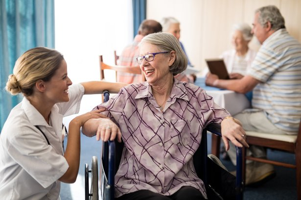 nurse attending to a cheerful elderly woman sitting in a wheelchair in a nursing home