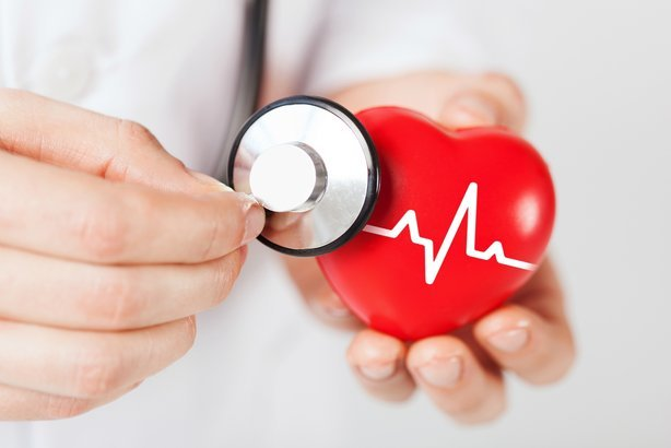 close up of male doctor hands holding red heart with ecg line and stethoscope