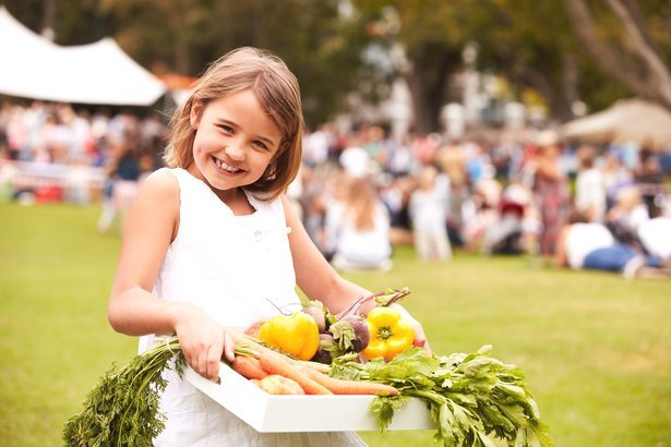 Girl with fresh produce at outdoor farmers market