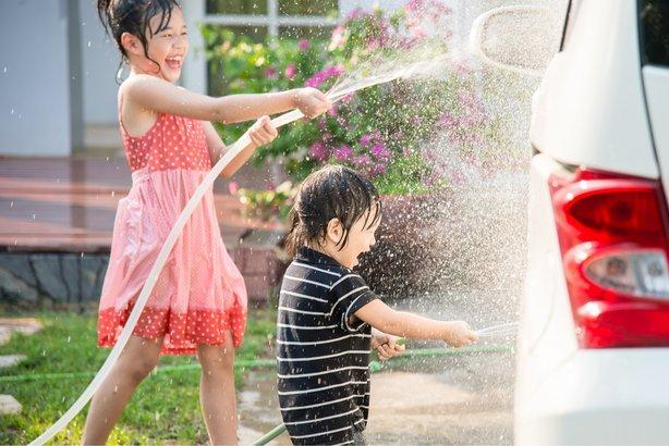 Asian children washing car in the garden