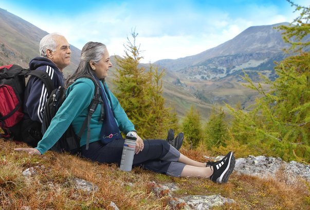 Old couple sitting on hill with hiking gear.