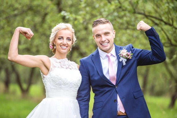 Beautiful young wedding couple outside in nature flexing muscles.