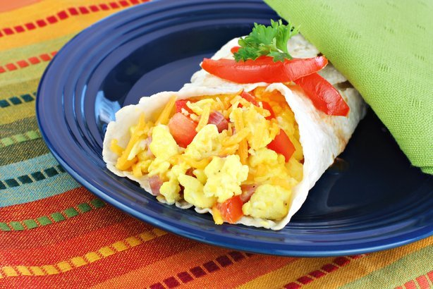 Delicious breakfast egg, tomato, cheese and pepper burrito