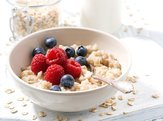 homemade oatmeal with berries on white wooden board