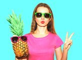pretty woman and pineapple with sunglasses over blue background