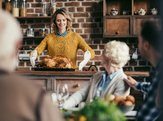 woman with Thanksgiving turkey for holiday dinner with family