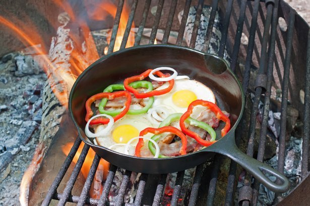 A breakfast of eggs on toast with bacon, onions and peppers frying on a grill