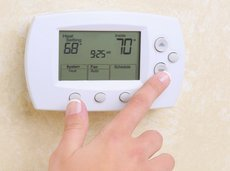 woman's hand setting the room temperature on a modern programmable thermostat