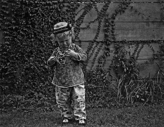 A toddler admiring her Mardi Gras beads, 1918